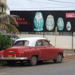 Vintage car; political billboard showing Hitler, Bush