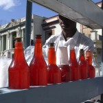 Typical street vendor selling drinks from red bottles on cart, Havana, Cuba, 2004