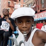Young boy with whistle wearing white cap celebrates African Day Parade, New York, NY 2008