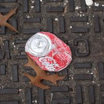 Coke-Cola can on manhole cover with leaves, New York, 2006