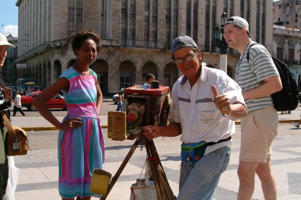 Street photographer makes instant photographs for visitors and locals, Havana, Cuba, 2004