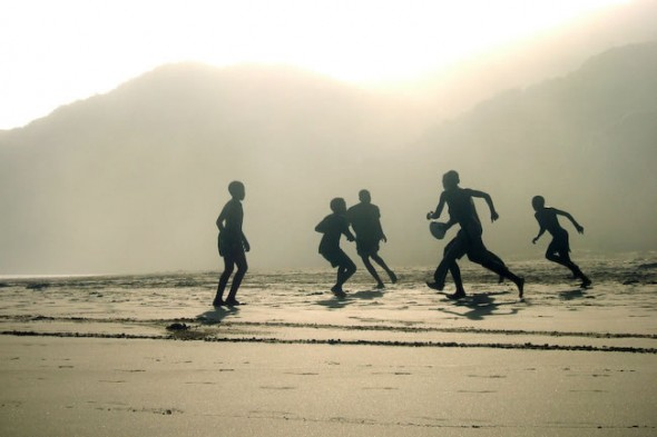 Children play rugby, at sunset on Kidds Beach, East London, South Africa, 2007